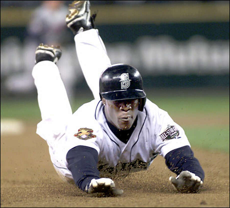 Mike Cameron slides into third with a triple in the fifth inning. He came around to score on Stan Javier's double as the Mariners finished a four-game sweep of the Angels. Photo: / Associated Press