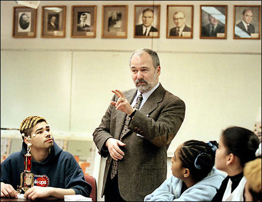 Len Aron, superintendent at the Washington School for the Deaf, congratulates students in sign language after they won a regional cheerleading trophy at a basketball tournament. Behind Aron are photos of past superintendents. Photo: Renee C. Byer/Seattle Post-Intelligencer