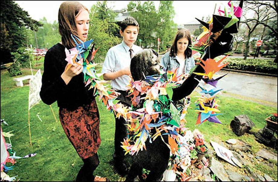 Ella, left, and Sara Schmoe, great-granddaughters of Seattle Peace Park founder Floyd Schmoe, help Felix Ostrom place origami on the park's statue of a Hiroshima victim. Photo: Dan DeLong/Seattle Post-Intelligencer