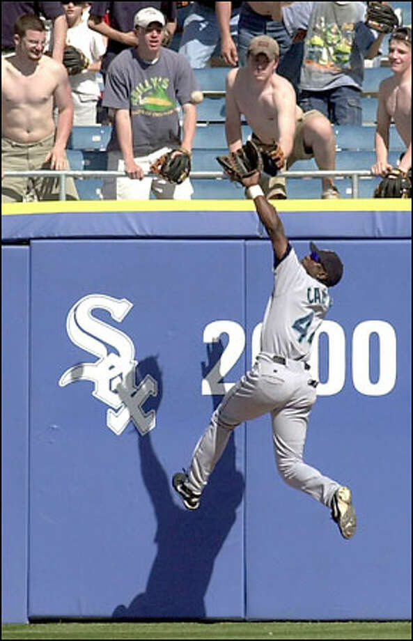 Mariners center fielder Mike Cameron knocks down Herbert Perry's 10th-inning home-run bid and renders it a harmless double. Photo: / Associated Press