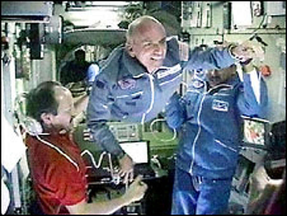 Space station commander Yuri Usachev, left, welcomes California millionaire Dennis Tito, center, and Russian cosmonaut Talgat Musabayev in this NASA TV photo.