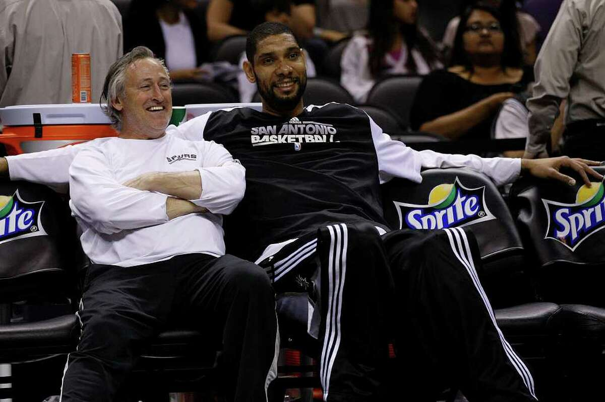 SPURS -- San Antonio Spurs Tim Duncan shares a laugh with Strenth and Conditioning Coach Mike Brungardt before their game aginst the Detroit Pistons at the AT&T Center, Wednesday, March 9, 2011. JERRY LARA/glara@express-news.net