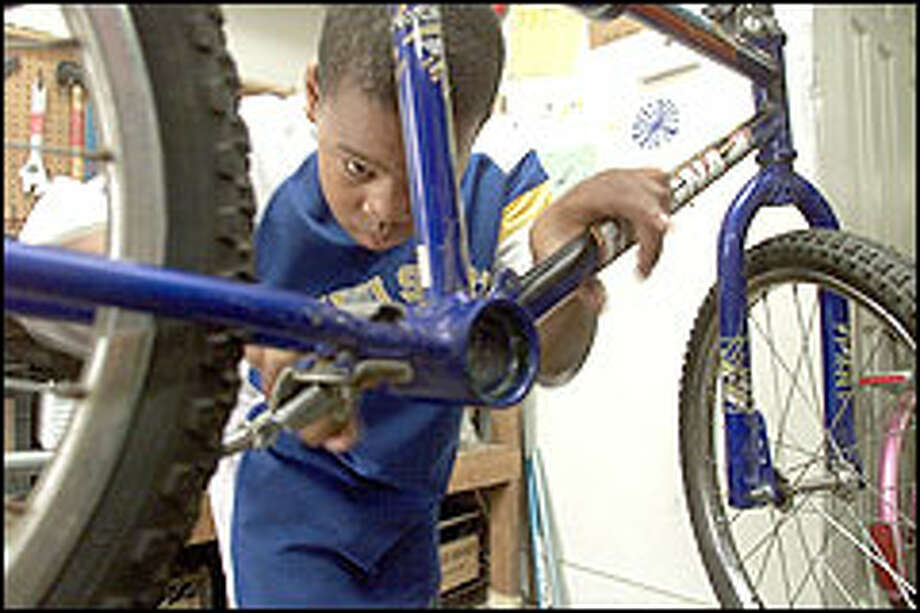 Kenny Harding, 9, works on a bicycle at Bike Works, a non-profit program in Rainier Valley. Photo: Paul Kitagaki Jr./P-I