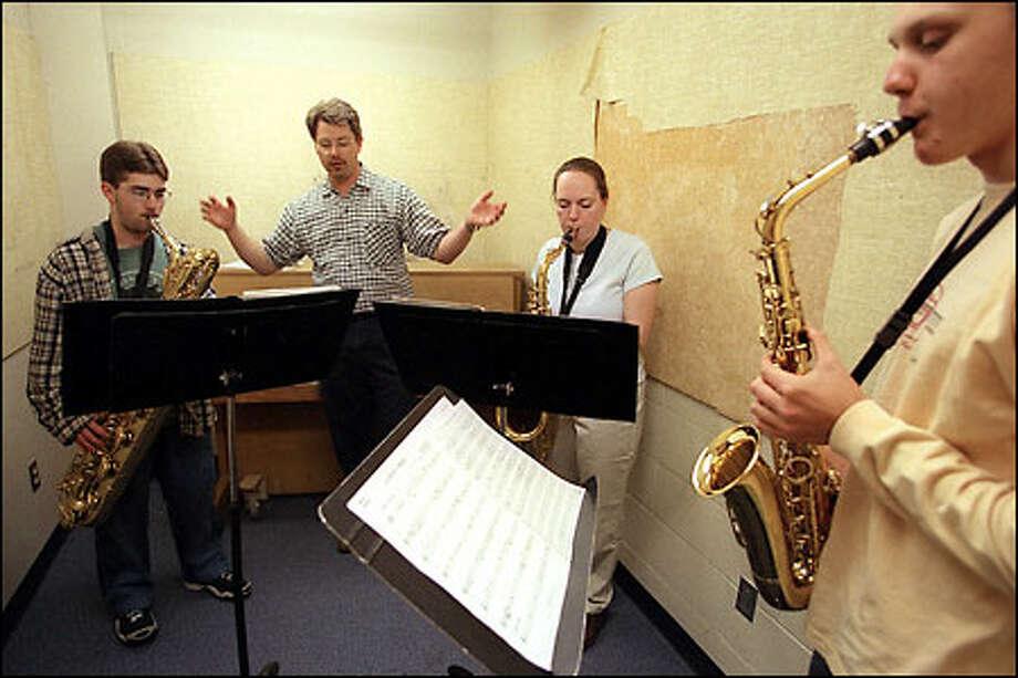 Matt Eisenhauer, the band director for Newport High School, works with saxophonists Brian Bruns, left, Christine Roach and Andrew Modelski. Photo: Meryl Schenker/Seattle Post-Intelligencer