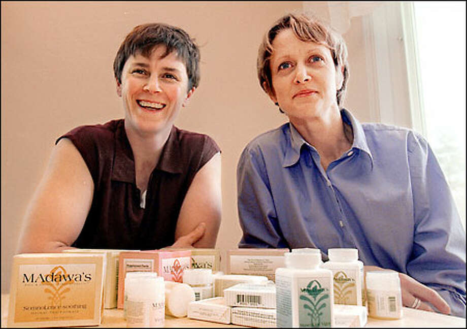 Penny Stone and Anita Schiltz, owners of Madawa's Pure and Natural Herbal Products, show off the wares that they import from Zanzibar. Photo: Phil H. Webber/Seattle Post-Intelligencer