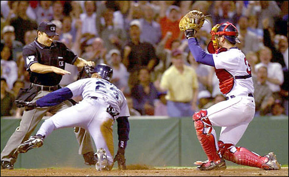 Boston catcher Jason Varitek holds up his mitt showing the ball as home plate umpire Mark Wegner calls Mariners baserunner Al Martin safe at home on a double by Carlos Guillen in the fifth inning. Varitek and manager Jimy Williams were ejected arguing the call. Photo: / Associated Press