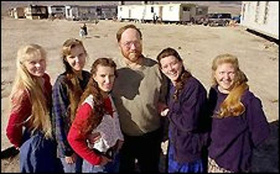 Tom Green, center, and his five wives pose at their homes in Trout Creek, Utah. The wives are, from left, Hannah, Lee Ann, Shirley, Linda and Cari. The state of Utah begins its first modern polygamy prosecution today with the trial of Green, who lives with his wives and their 29 children in the Utah desert. Photo: AP PHOTO