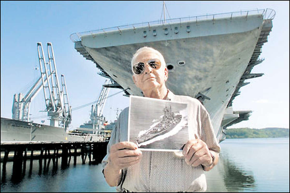 Standing in front of the USS Independence in Bremerton, Bud Higgs, a retired Navy boatswain's mate, holds a picture of the USS Washington. Higgs served on the Washington, a distinguished but little-known World War II battleship.