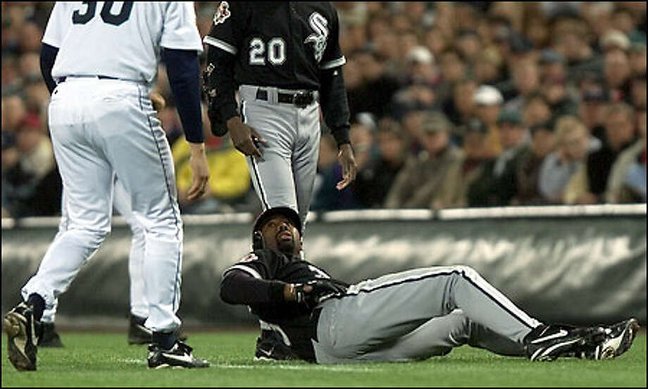 White Sox outfielder Harold Baines stares at Mariners pitcher Aaron Sele after colliding with him following Sele's play on a grounder  in the third inning. Photo: Paul Kitagaki Jr./Seattle Post-Intelligencer