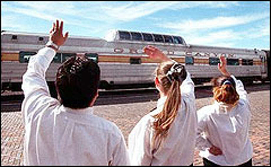 Employees from Max and Thelma's Restaurant wave farewell to Grand Canyon Railway passengers as they leave the depot at Williams, Ariz. Photo: Jake Bacon