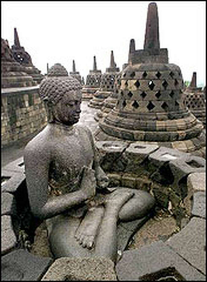 A statue of Buddha resides on a terrace of 1,100-year-old Borobudur temple on Java Island. The giant monument, composed of six square terraces and three circular ones stacked upon each other to form a pyramid, was restored by Dutch colonizers in the past century and is now a World Heritage Site. Photo: AP