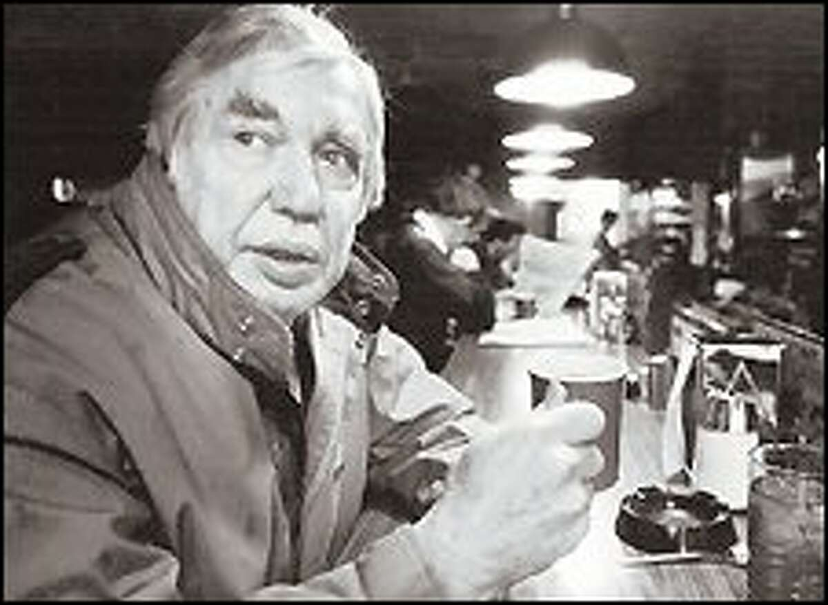Emmett Watson enjoys a cup of joe at one of his favorite Seattle hangouts, the Mecca Cafe. A P-I columnist for 33 years, Watson ended his career at the Seattle Times.