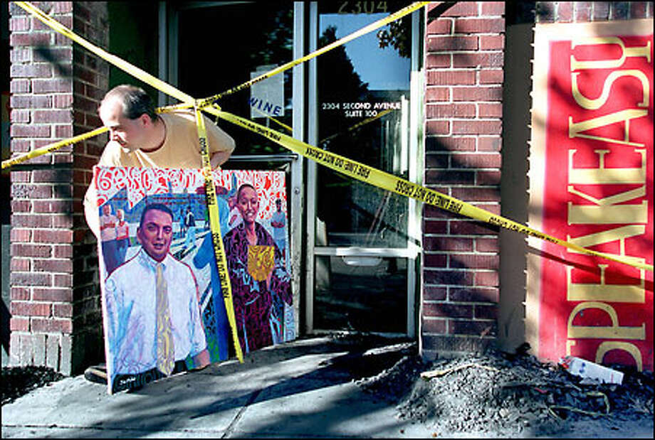 Artist Jim Porter, whose acrylic works were chosen to brighten the Speakeasy Café, removes one of his paintings from the burned-out business. He left several for insurance assessment. Photo: Renee C. Byer/Seattle Post-Intelligencer