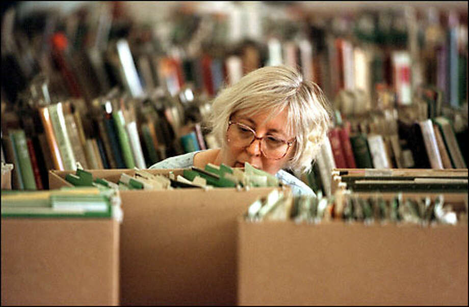 Master Gardener Carol Judge helps sort through some of the files and books salvaged from Monday's arson fire at the UW Center for Urban Horticulture. Photo: Gilbert W. Arias/Seattle Post-Intelligencer