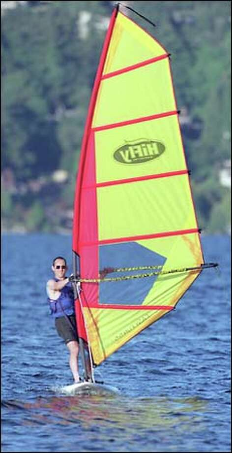 Harnessing the breeze, windsurfing student Marc Kriger of Seattle is all smiles as he skims across Lake Washington. Photo: Grant M. Haller/Seattle Post-Intelligencer