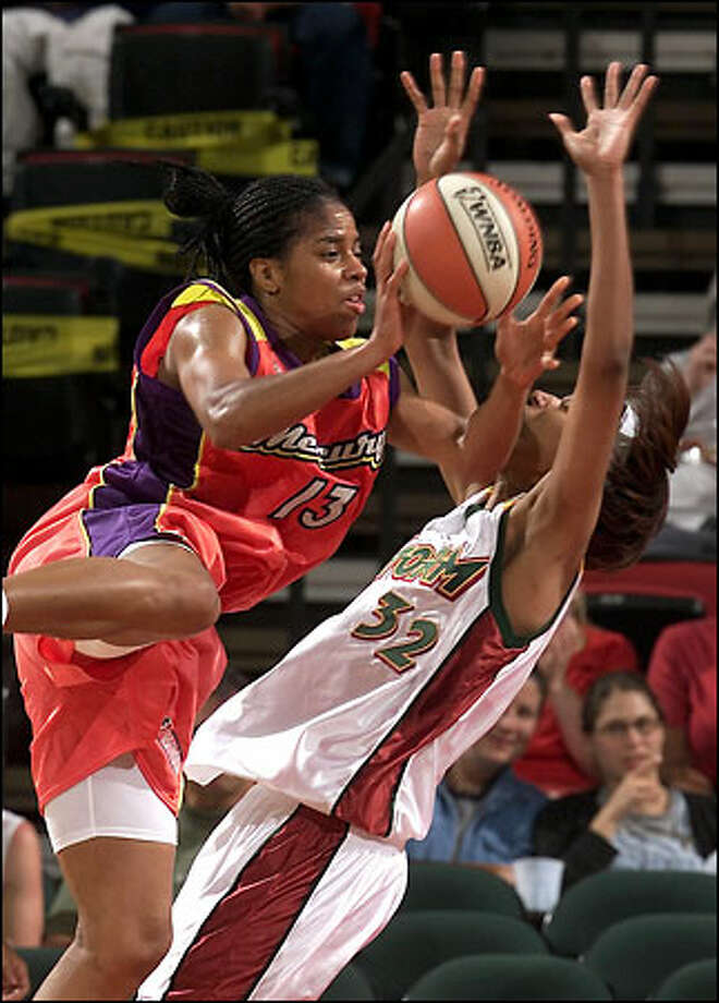 Tonya Edwards of the Phoenix Mercury picks up a foul as she charges over Stacey Lovelace during the second half. Photo: Paul Kitagaki Jr./Seattle Post-Intelligencer