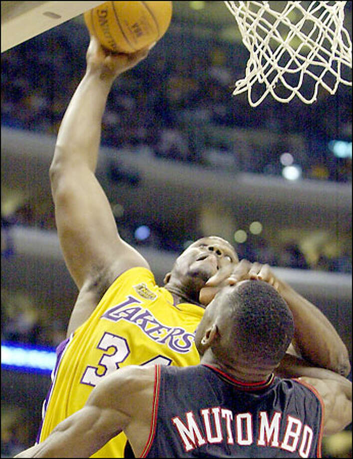 The Lakers' Shaquille O'Neal shoves aside the 76ers' Dikembe Mutombo as he throws down a dunk during the second half. O'Neal finished with 44 points. Photo: / Associated Press