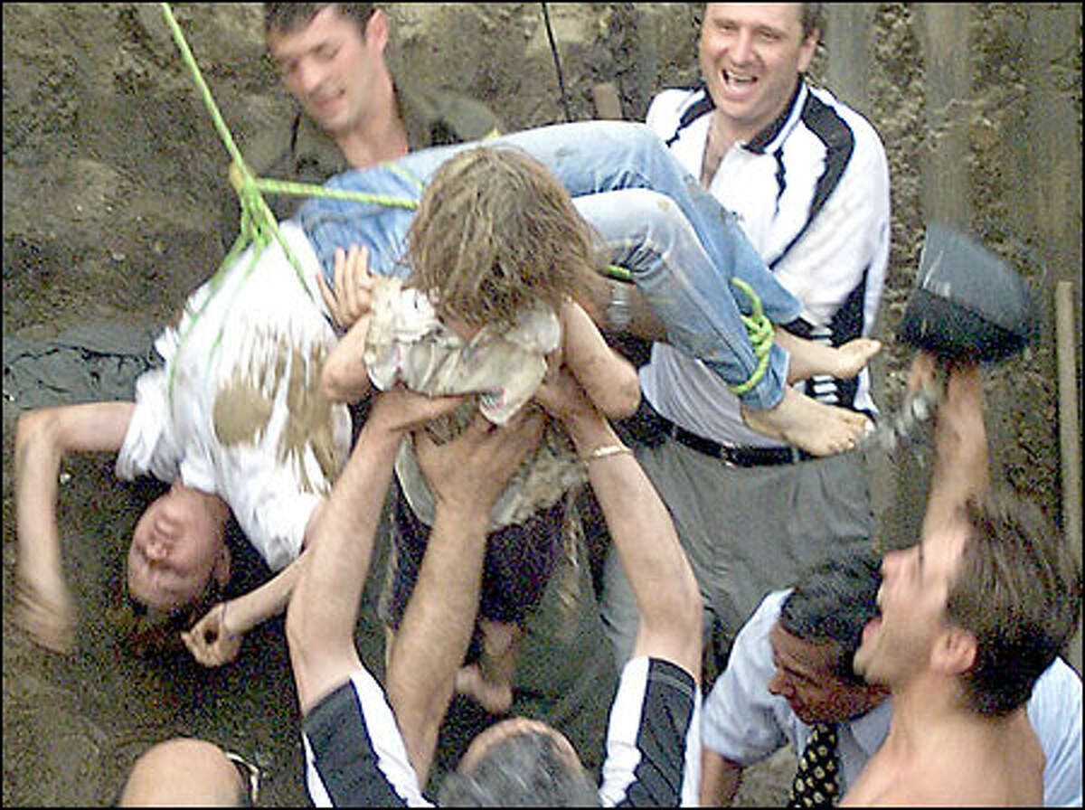 Two-year-old Alina Pascaru, center, is held by cheering rescue workers after she was plucked from a water well by teenage volunteer rescuer Oana Furnica, left, in Romania.