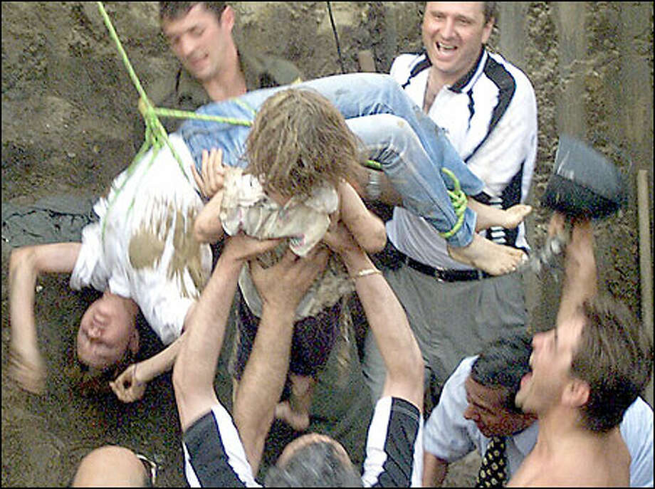 Two-year-old Alina Pascaru, center, is held by cheering rescue workers after she was plucked from a water well by teenage volunteer rescuer Oana Furnica, left, in Romania. Photo: / Associated Press