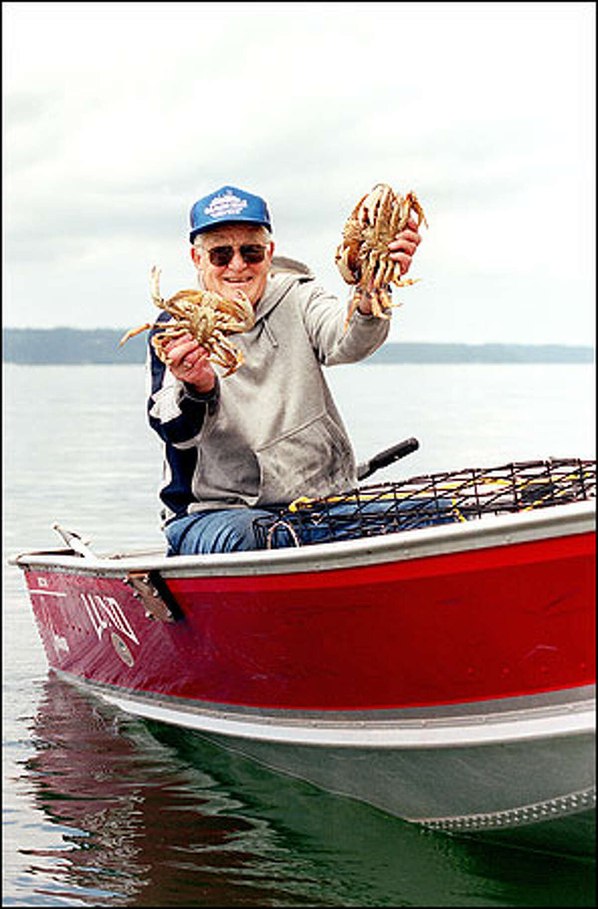 """Owen """"Mike"""" Hunt shows off some of the Dungeness crabs he caught near his Camano Island home."""