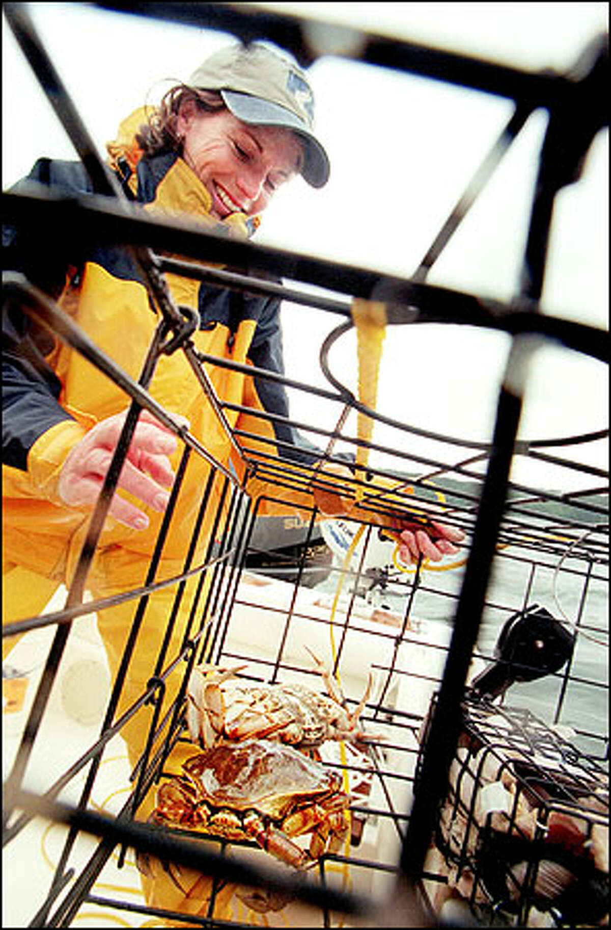 Karyl Beyerle checks her catch after pulling in a pot from lower Hood Canal near Hoodsport.