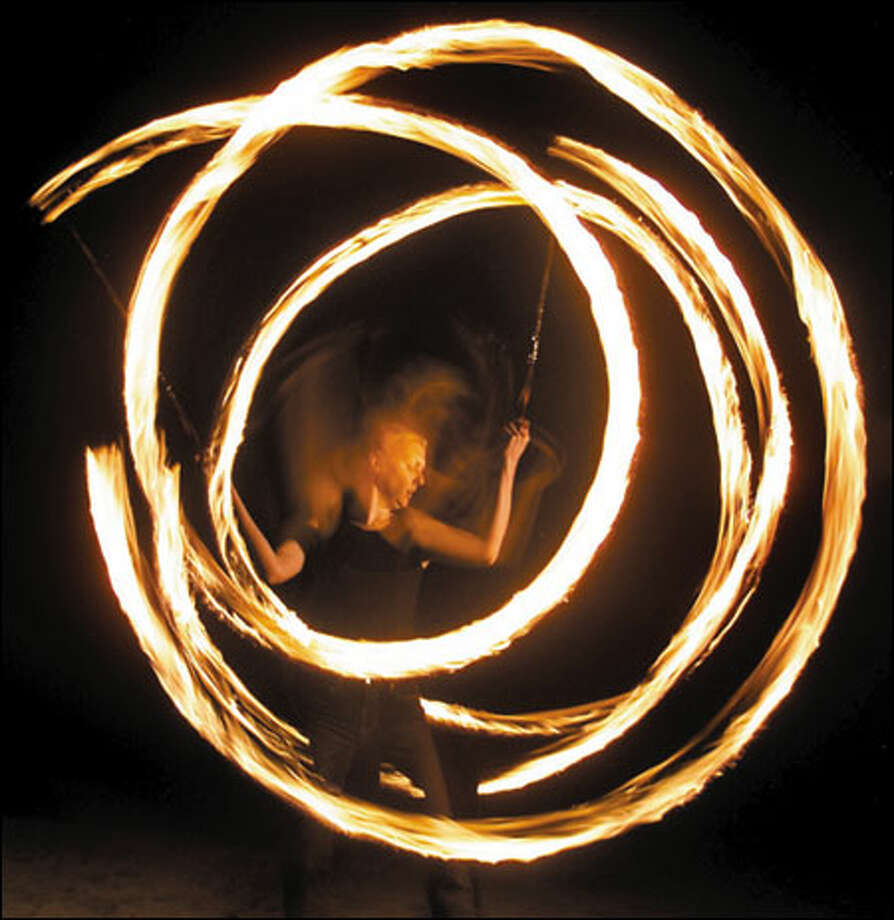 """The power of fire is intense,"" says Kat Martin, a member of Pyrosutra and one of a growing number of Seattle residents who have recently taken up fire spinning. Photo: Mike Urban/Seattle Post-Intelligencer"