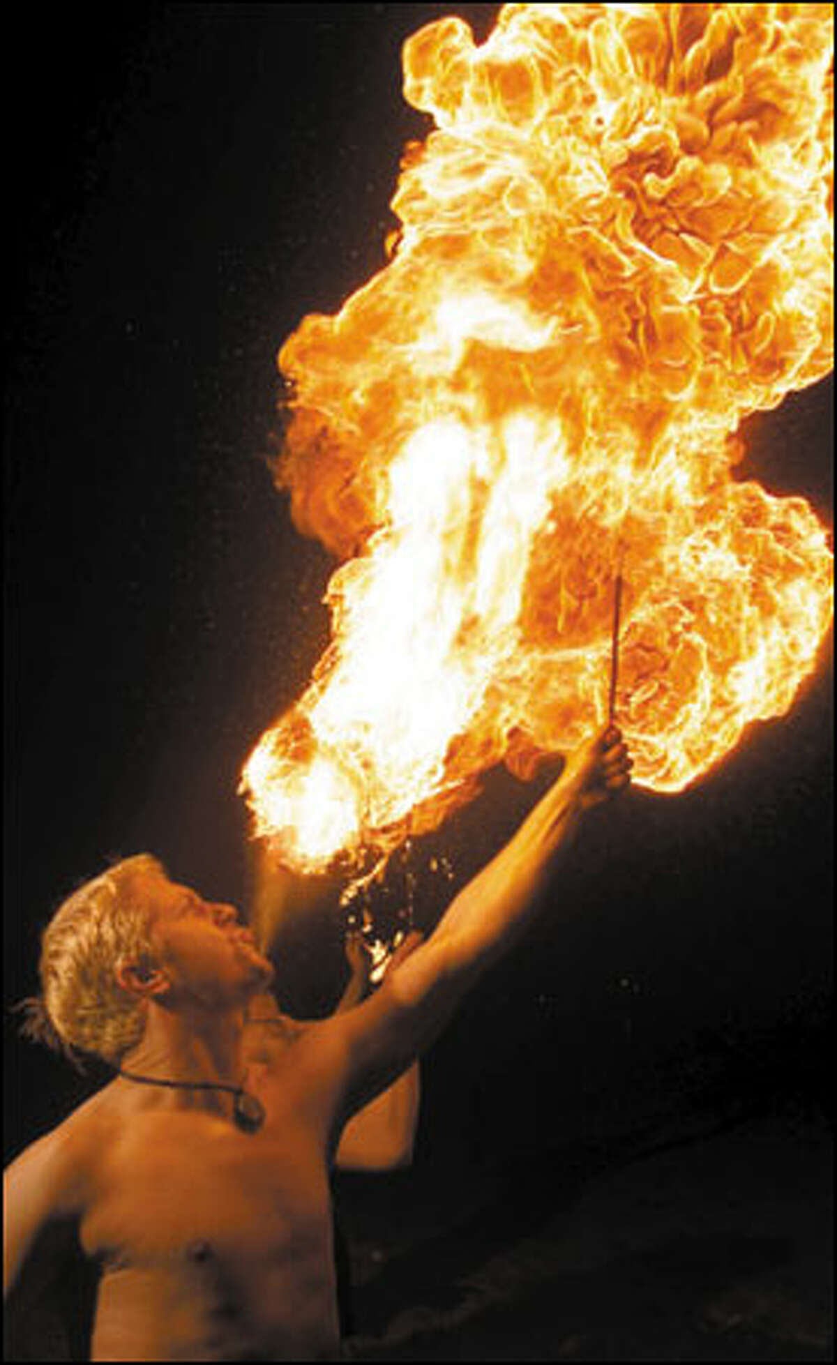 Adam Henderson performs fire blasts. Blowing fire is among the most dangerous fire arts because of the risk to the face and lungs and because the body absorbs the toxic fuel used to make the blaze through the mouth and gums.