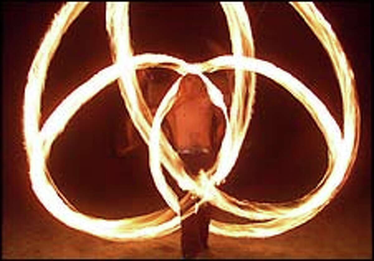 Chris Airola of Pyrosutra, spins fire.
