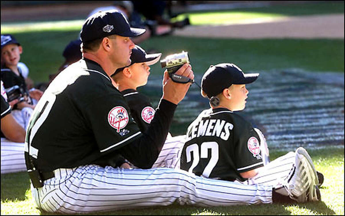 Yankees pitcher Roger Clemens sits with his sons while videotaping the Home Run Derby. Clemens (12-1) starts for the American League tonight.