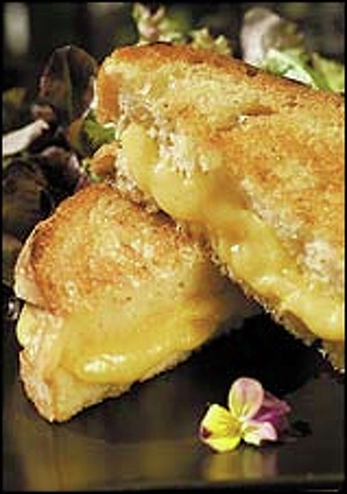 One of the premium American comfort foods is the grilled cheese sandwich, often served with tomato soup.