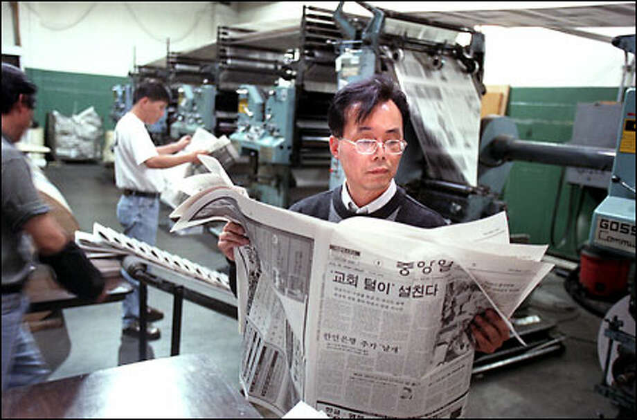 Dong Keun Lee, editor in chief of The Korea Central Daily Northwest Branch, reads his daily hot off the press. It faces stiff competition from the Korea Times. Photo: Paul Joseph Brown/Seattle Post-Intelligencer