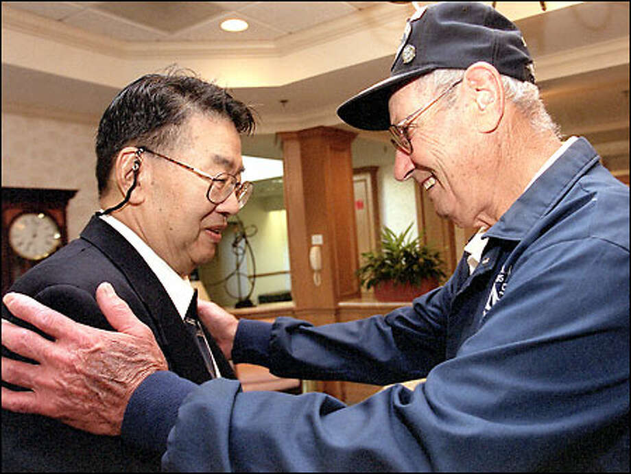 Ken Nakano, in Hiroshima when the atomic bomb exploded, greets Eugene Morgan, who served on the Indianapolis, which took the bomb to the Pacific. Photo: Phil H. Webber/Seattle Post-Intelligencer