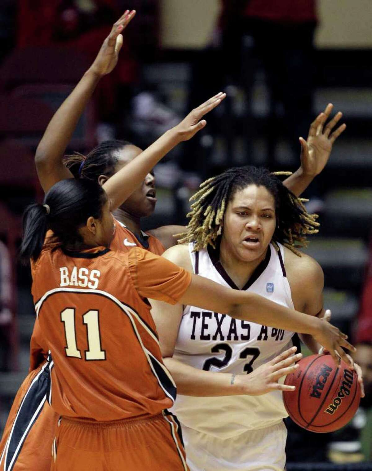 Texas A&M's Danielle Adams, right, tries to find her way around Texas' Chelsea Bass (11) and Ashley Gayle, rear, during the second half of an NCAA college basketball game at the Big 12 Conference women's tournament on Wednesday, March 9, 2011, in Kansas City, Mo. Texas A&M won 77-50.