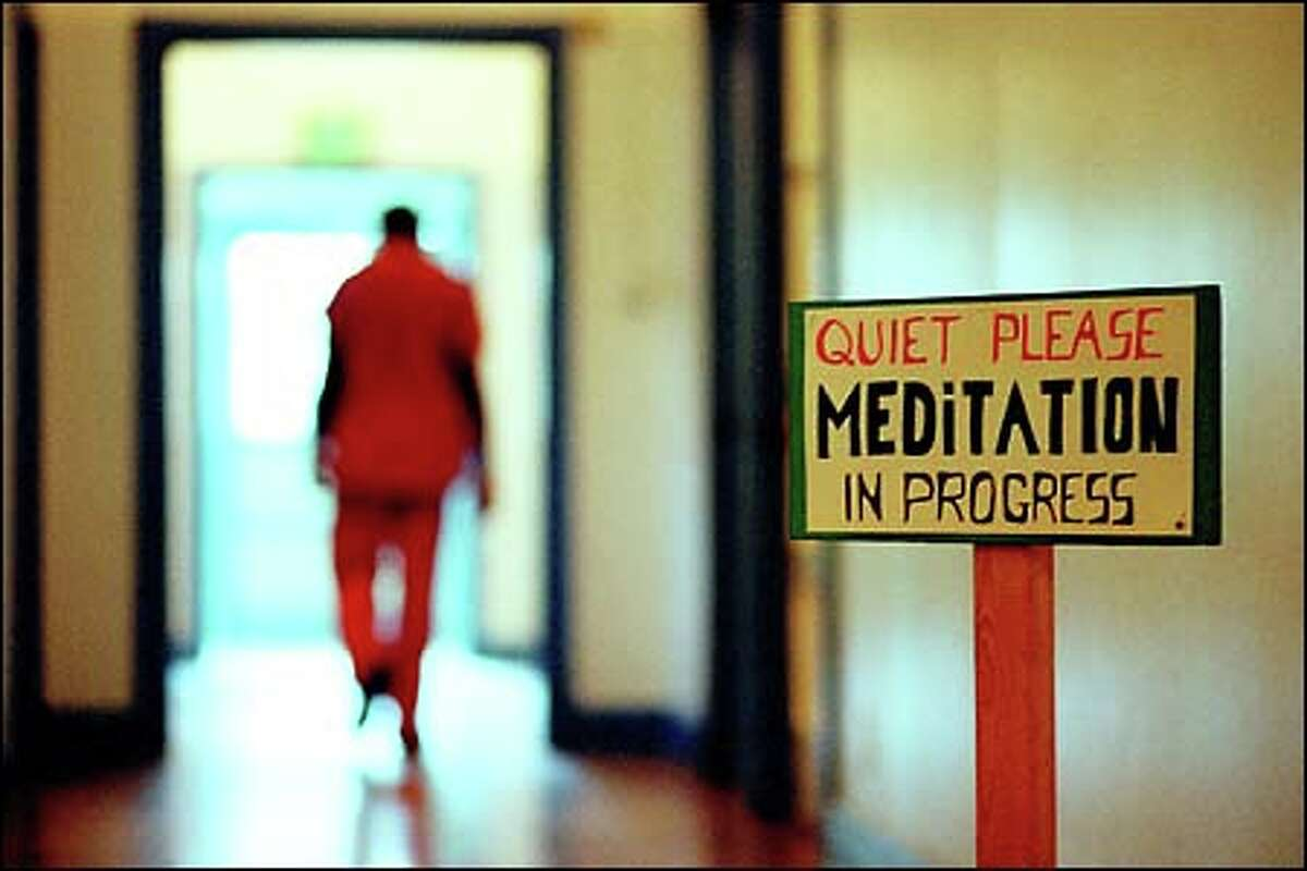 A resident of the Northern Rehabilitation Facility in Shoreline walks past a room where other inmates are meditating.