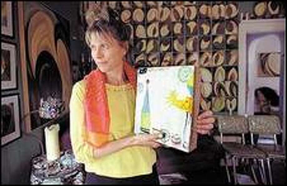 Susanna Dent has learned that artwork can sometimes be exchanged for a person's life. She holds one of her paintings similar to the one she handed over to her mugger. Click for a larger image Photo: GILBERT W. ARIAS/P-I