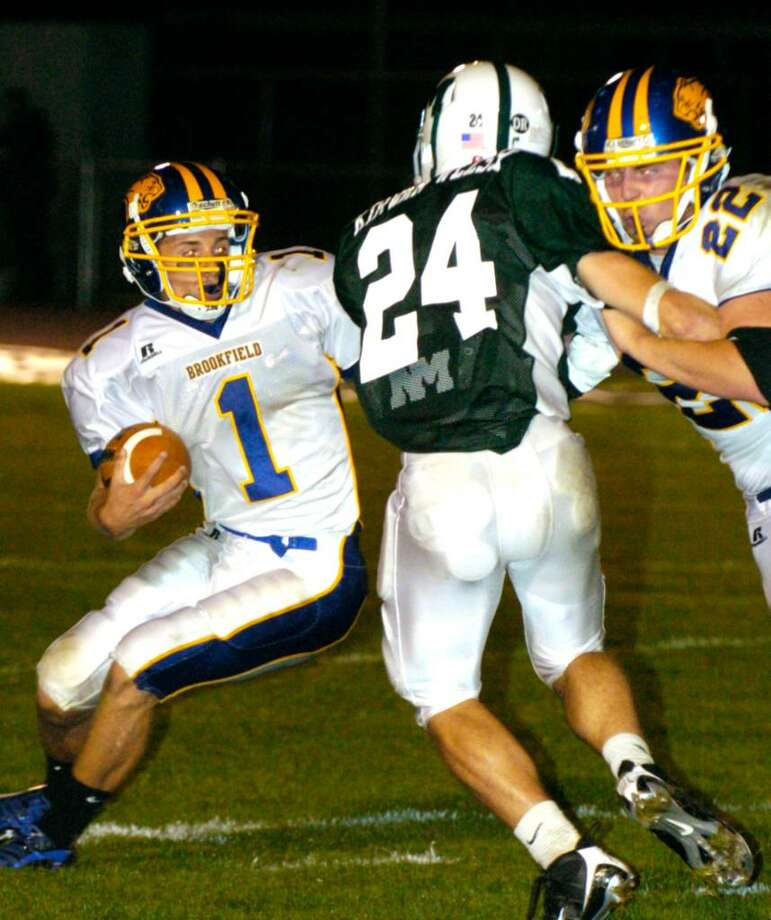 Brookfield's 1, Jordan Burandt heads upfield while New Milford's 24, Brian Kirwan-Welsh trys to block unsuccessfuly as Brookfield's 22, Michael Palicz steps in at the football game in New Milford Wednesday, Sept. 16, 2009. Photo: Chris Ware / The News-Times