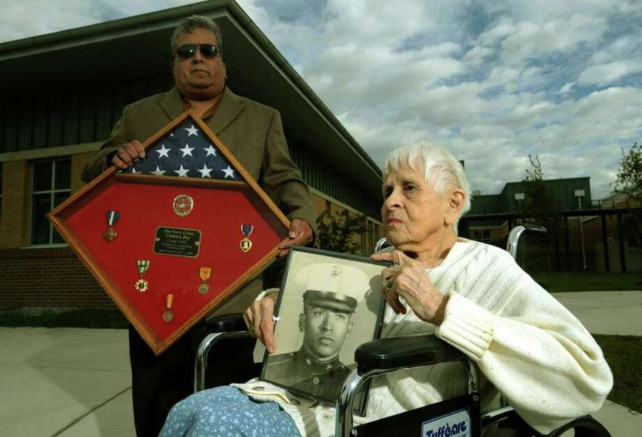 James Cisneros and his mother, Elvira, 85, hold a photo and medals belonging to Marine Cpl. Roy Cisneros, who died in Vietnam on Sept. 11, 1968. Photo: BILLY CALZADA, SAN ANTONIO EXPRESS-NEWS