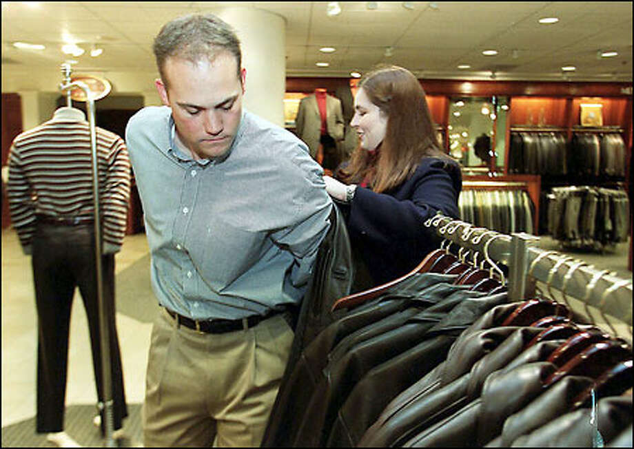 "Erin Paretich, a personal shopper for Nordstrom, at right, helps customer Barry Barnes try on a ""business-casual"" leather jacket. Photo: Phil H. Webber/Seattle Post-Intelligencer"