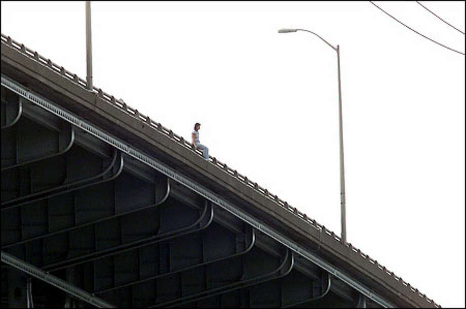 High above the Ship Canal, a distraught 26-year-old woman sits on the southbound railing of the Interstate 5 bridge yesterday morning after leaving her car. Photo: Meryl Schenker/Seattle Post-Intelligencer