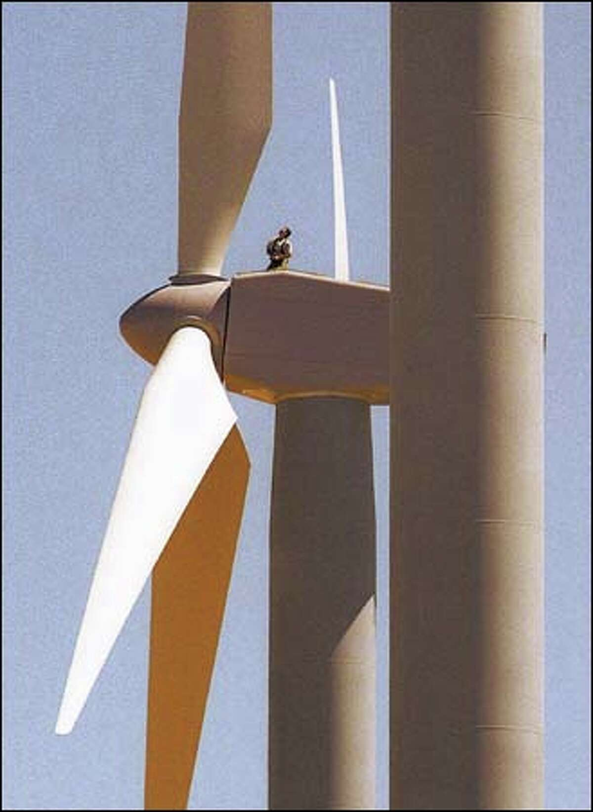 A tethered worker at FPL Energy's Stateline Wind Project on Hatch Grade near Wallula Junction prepares to make a blade readjustment on a 24-story wind turbine, one of 450 that will produce energy at the site.