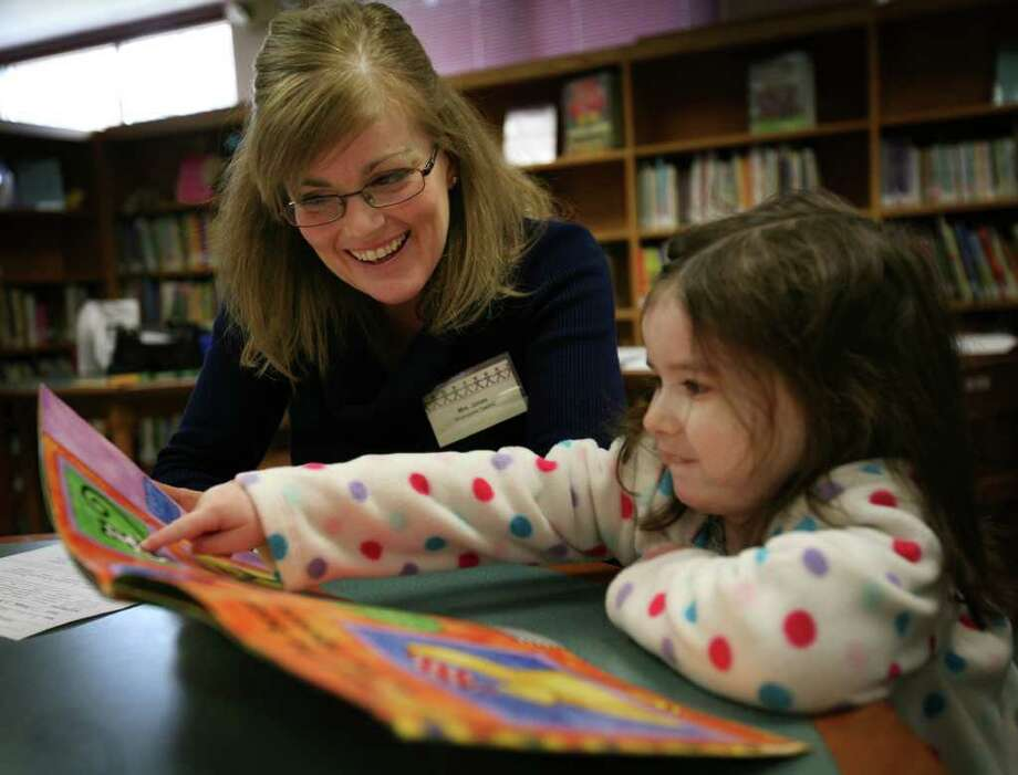 Kindergarten teacher Carol Jones looks at a children's book with Kaylee Hannon, 4, during kindergarten registration at John F. Kennedy School in Milford on Wednesday, March 9, 2011. Photo: Brian A. Pounds / Connecticut Post