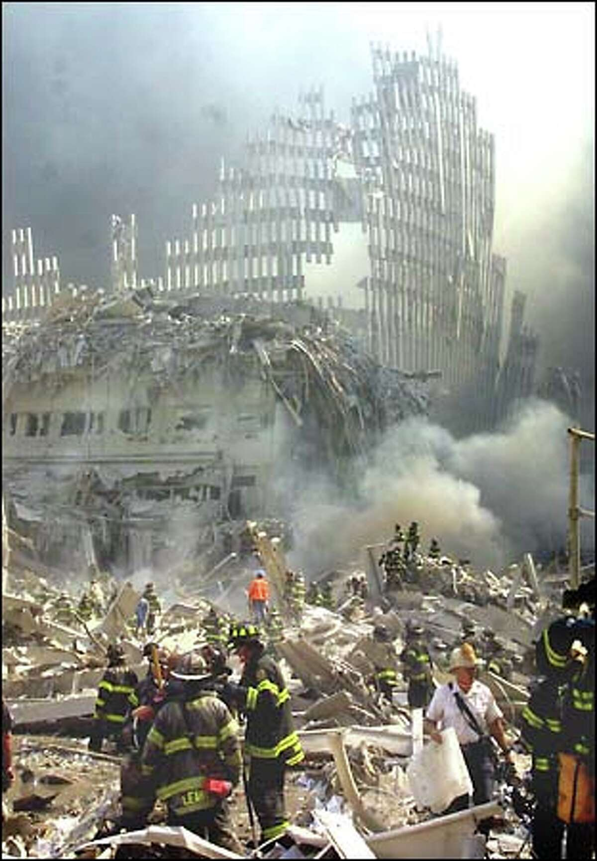 Rescue workers scramble through the rubble of the collapsed World Trade Center. A shell of the destroyed landmark looms in the background.