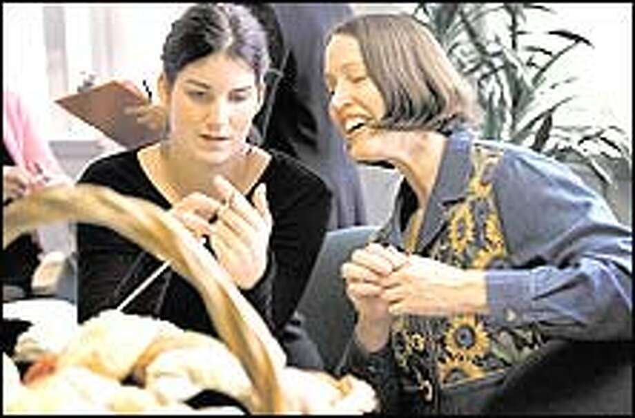"""Brooke Fennerty, 17, a family member of a cancer patient at the UW Medical Center, gets a knitting lesson from Lynn Sitton of Edmonds, right, who joined the group when she got cancer 2 1/2 years ago. """"This is the one thing I have hung on to after going through treatment,"""" Sitton said. Photo: Renee C. Byer/P-I Photo"""