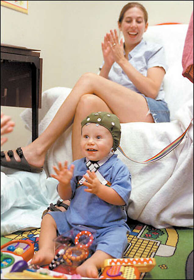 Samuel Dodd, 11 months, gets ready to participate in an event-related experimental session at the University of Washington to study speech perception. Behind him is his mom, Janine Dodd of Auburn. Photo: Meryl Schenker/Seattle Post-Intelligencer