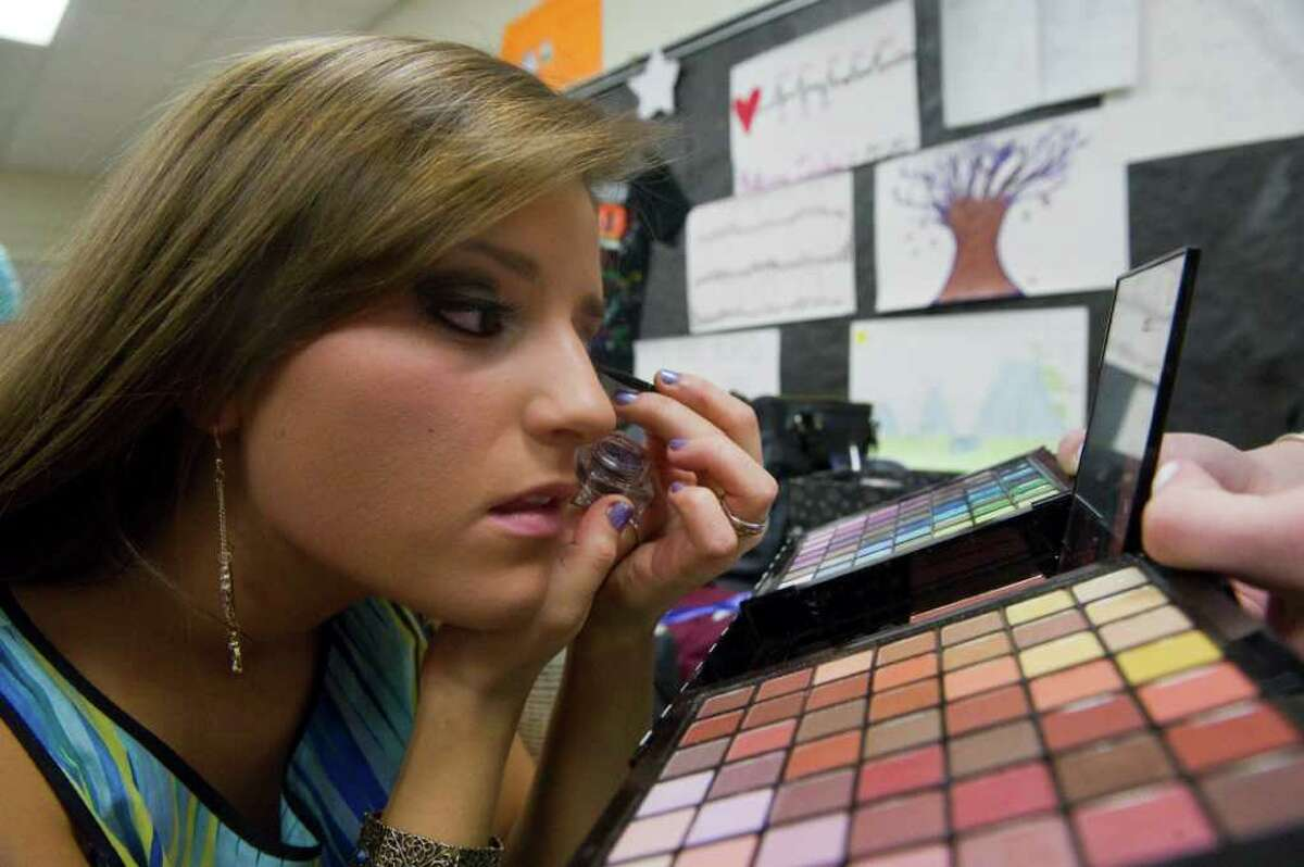 Jessy Biagini puts the finishing touch on her look as she prepares for the runway at Stamford High School in Stamford, Conn., March 10, 2011. The ?'Saturday Knight Fever?