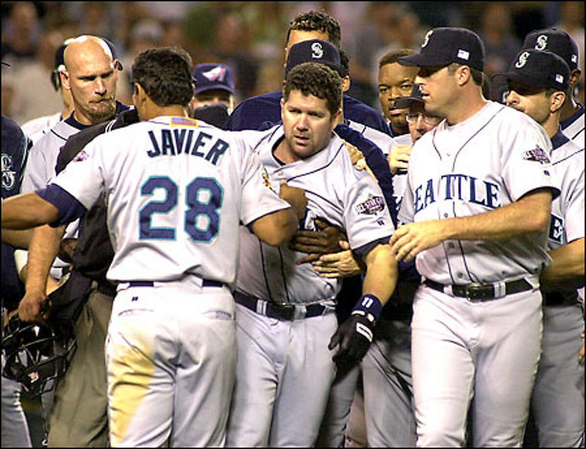 Edgar Martinez is restrained by his teammates after getting into a sixth-inning scuffle with Angels pitcher Lou Pote. Martinez charged the mound after being hit by a pitch and was ejected.
