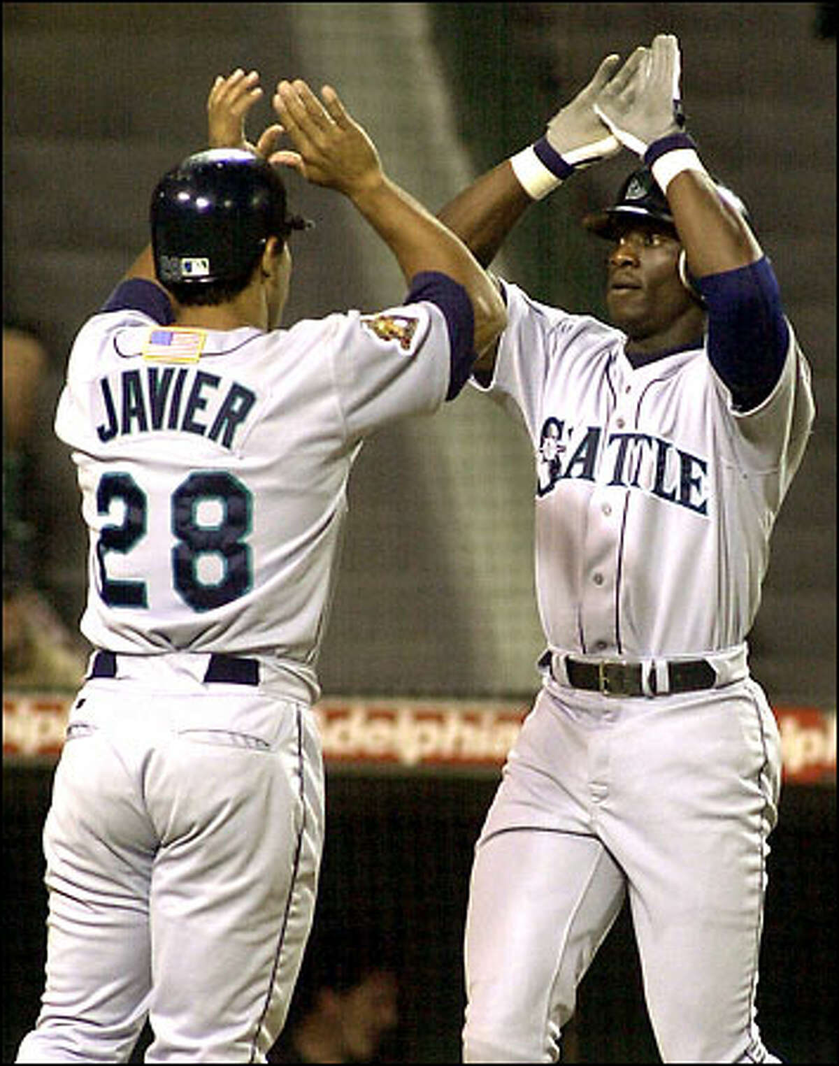 Mike Cameron slaps hands with Stan Javier after hitting a three-run home run against the Angels in the fourth inning.