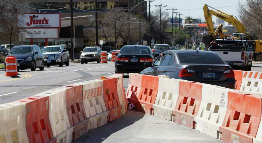 Traffic works its way around barricades on Broadway near the intersection with Hildebrand Avenue. Lanes have been closed on Broadway in the vicinity of the University of the Incarnate Word. Photo: WILLIAM LUTHER, William Luther/Express-News / SAN ANTONIO EXPRESS-NEWS