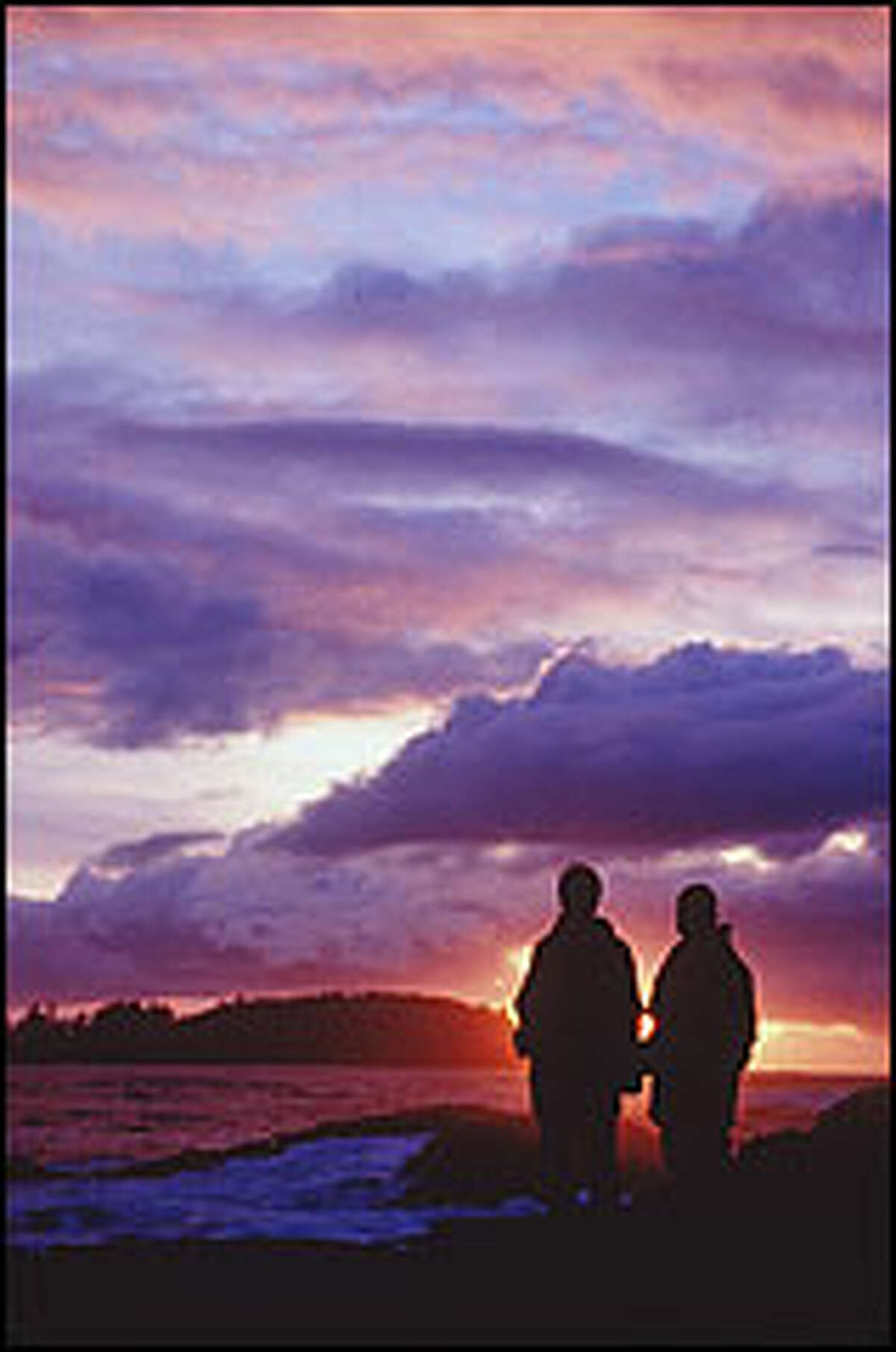 Sunset silhouettes a pair of storm watchers near the Wickaninnish Inn on Vancouver Island's wild west coast.
