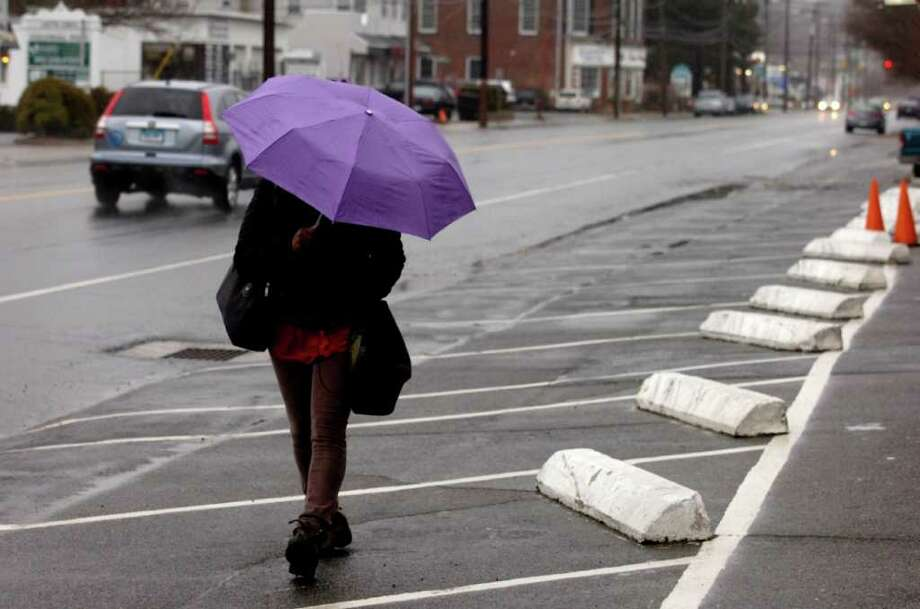 Ruth Davenport hides under an umbrella as she walks to the train station in Fairfield on Thursday, March 10, 2011. Photo: Lindsay Niegelberg / Connecticut Post